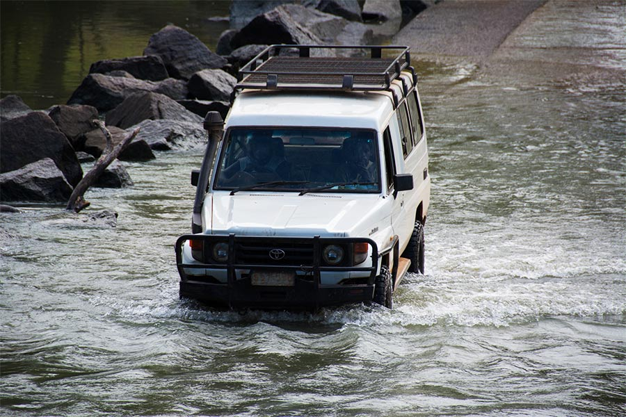 Vehicle going through water with a full-length roof cage attached to it