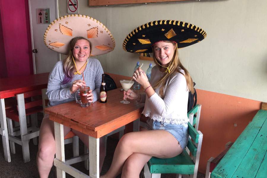 Two women drinking alcoholic beverages in a cafe wearing sombreros on their heads