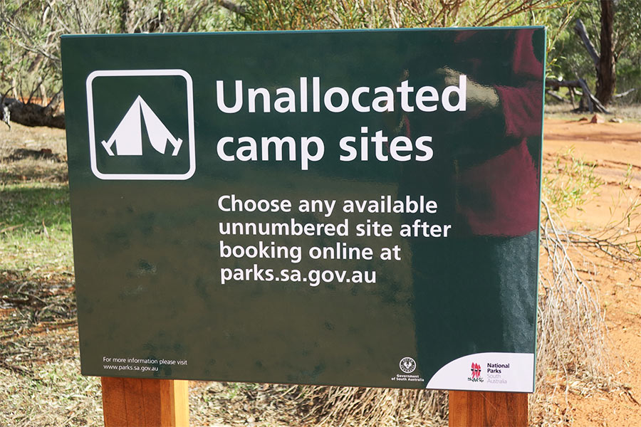 An Unallocated camp sites sign giving instructions on how to book a campsite
