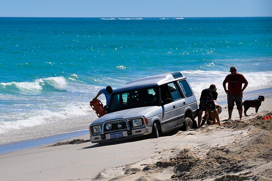 People trying to unblog a 4WD stuck on the beach