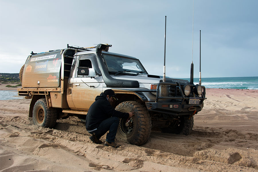 Man adjusting tyre pressure on 4WD to prevent his vehicle from getting bogged whilst driving