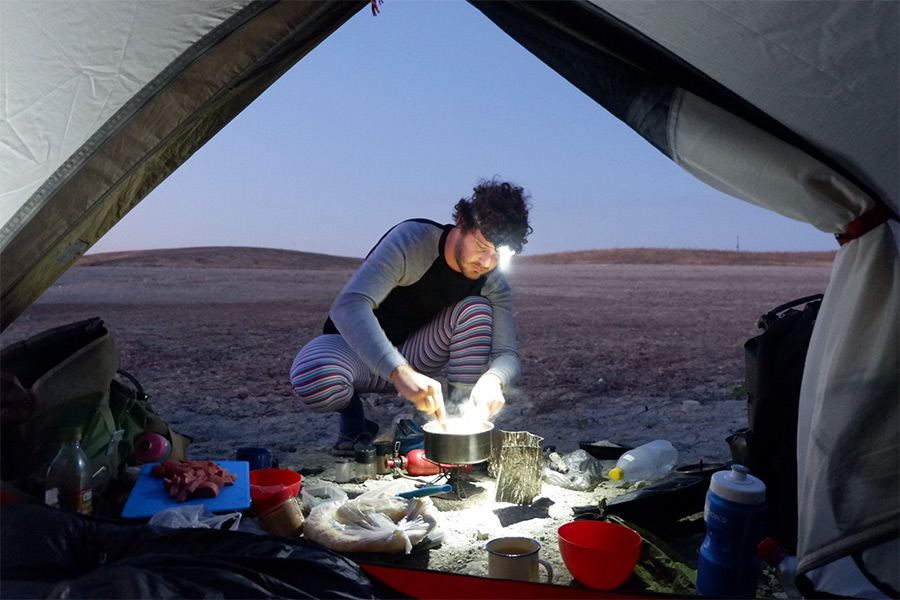 Man cooking on a hiking stove near a tent at dusk
