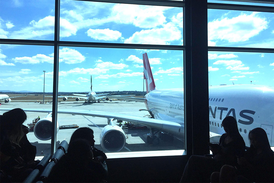 View of a QANTAS plane from inside an airport terminal