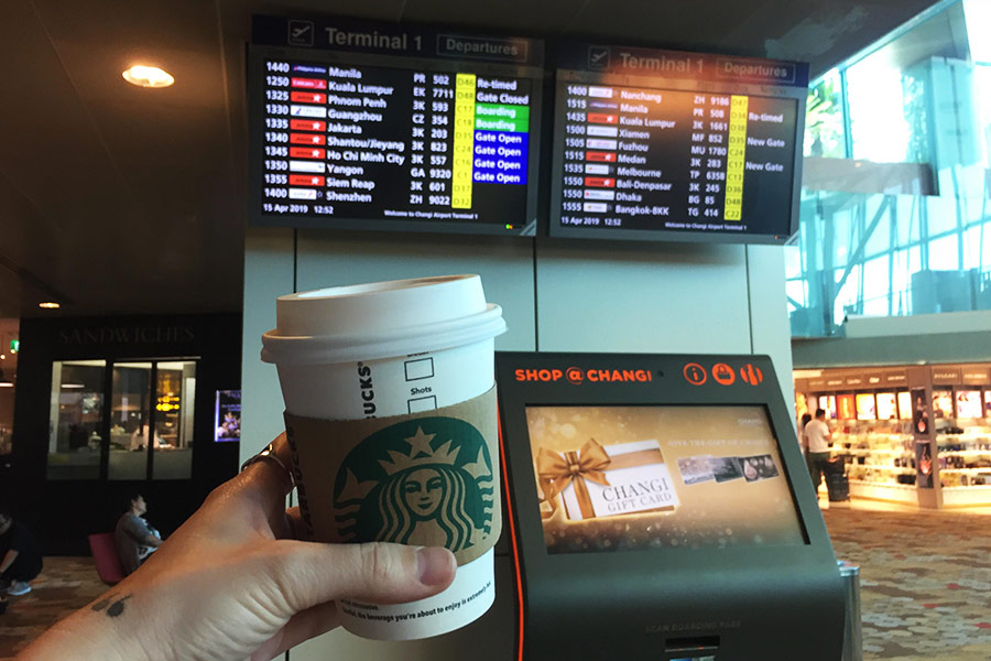 View of Starbucks coffee with screen display of airport arrival and departure times