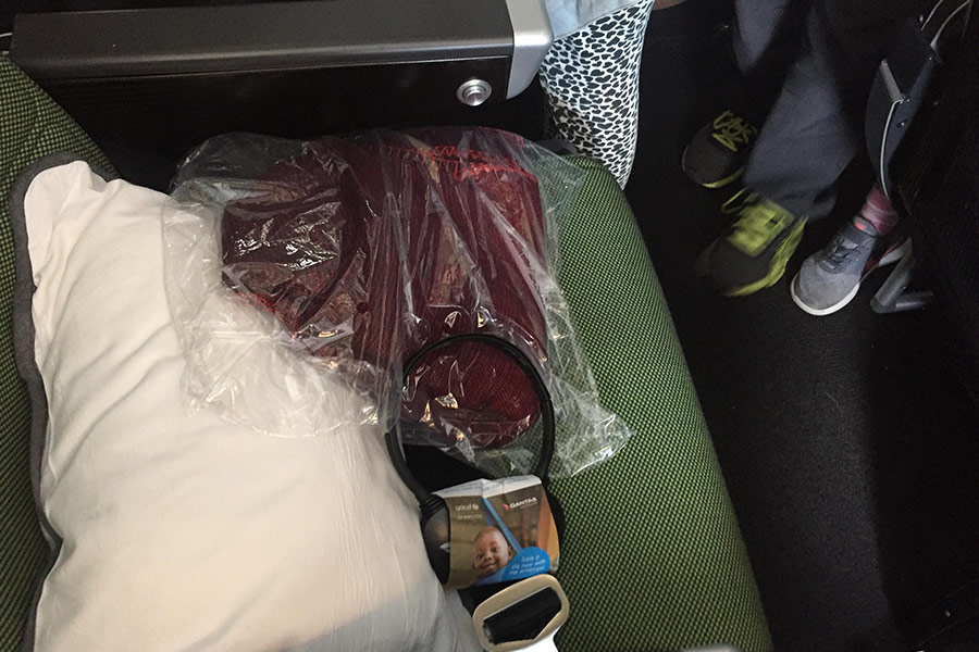Pillow, blanket and headphones resting on a plane seat