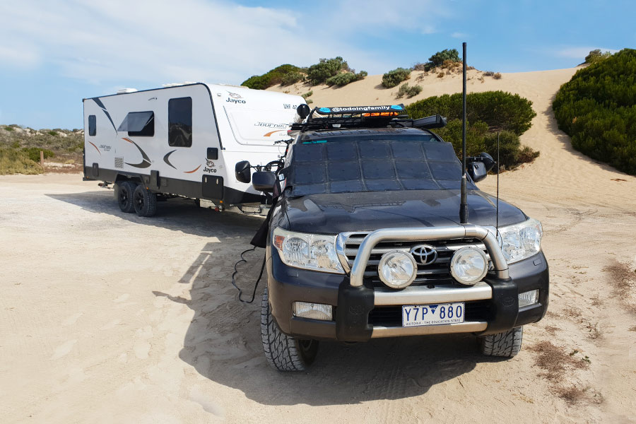 4WD towing caravan along beach road