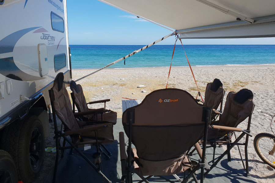 Oztent chairs setup outside caravan under awning on beach