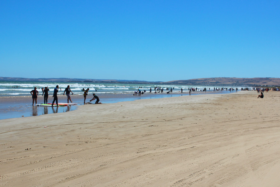 Swimmers and surfers enjoying the sand and water at Goolwa beach on a warm day.