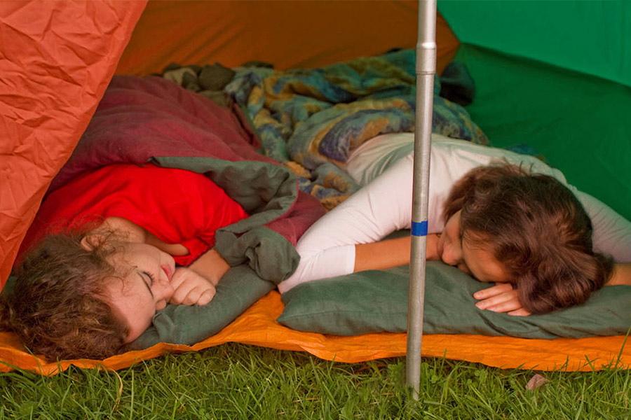 Two teenagers asleep in sleeping bags in a tent