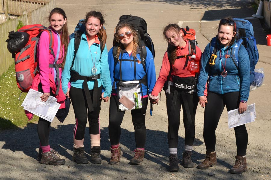 Teen girls wearing hiking gear, including hiking socks & boots