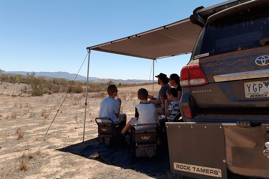 Family sitting outside at table under 4WD awning