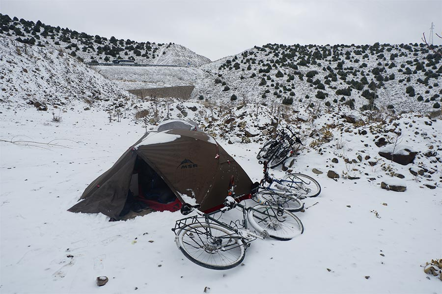Snow surrounding hiking tent and bikes