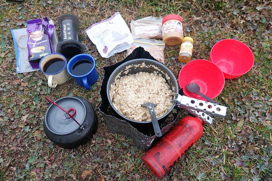 Aeropress portable coffee maker next to 2 mugs of coffee, food and cookware for outdoors
