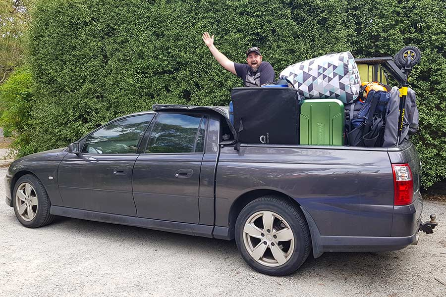 Man waving next to packed out Ute - full of camping supplies.