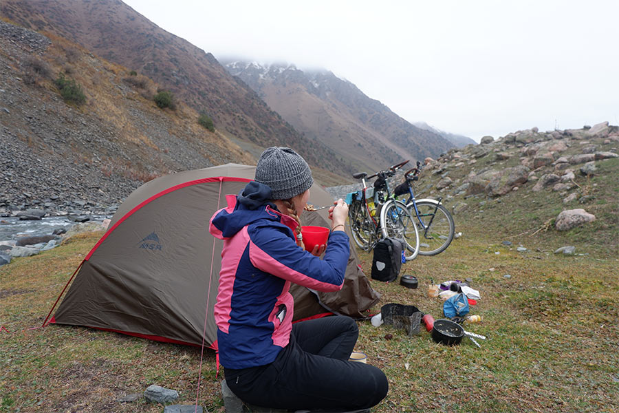 Woman eating next to her tent, bikes and gear in the outdoors