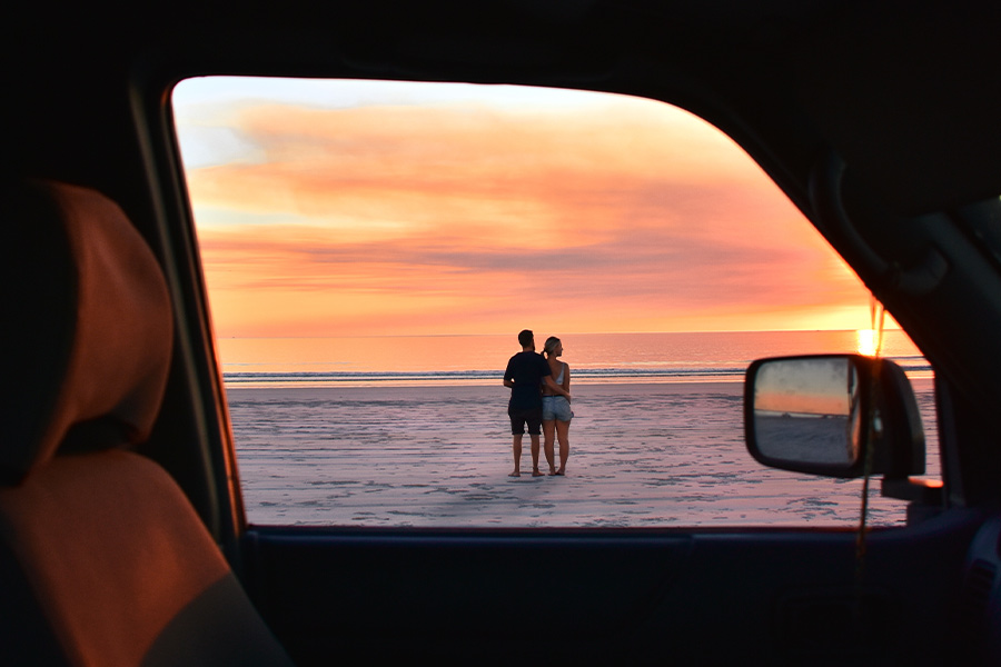 Couple cuddling and looking out over the ocean at Cable Beach at sunset