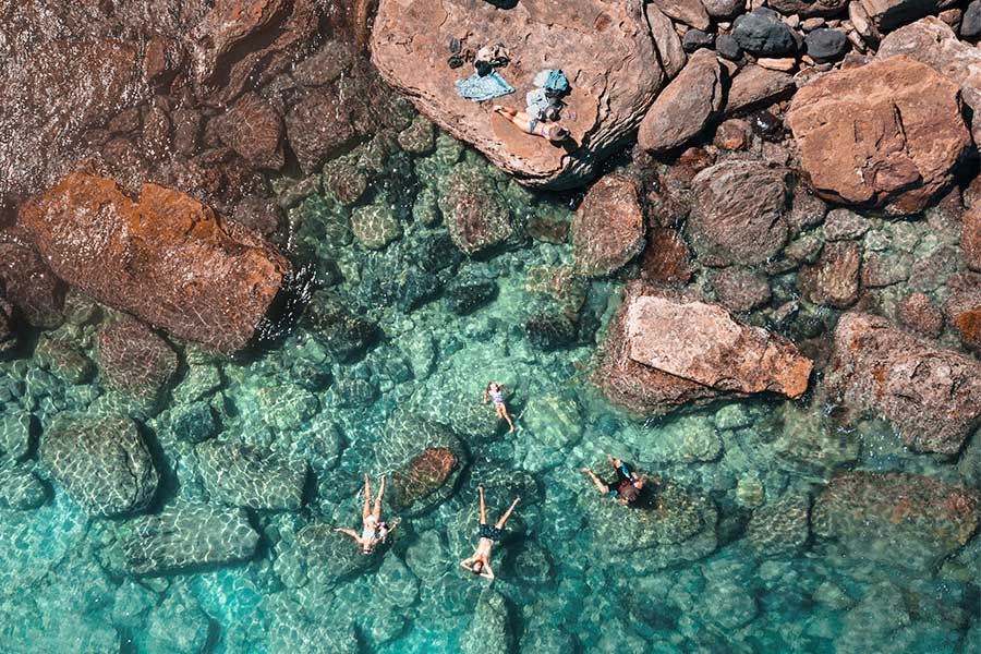 People swimming in the turquoise waters off Gantheaume Point