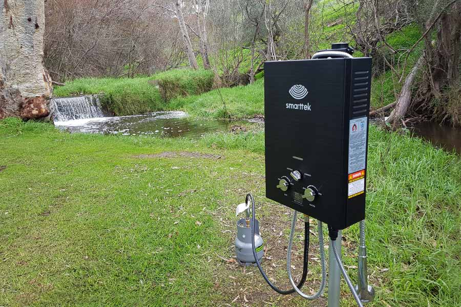 Smarttek black hot water system outdoors nearly flowing creek