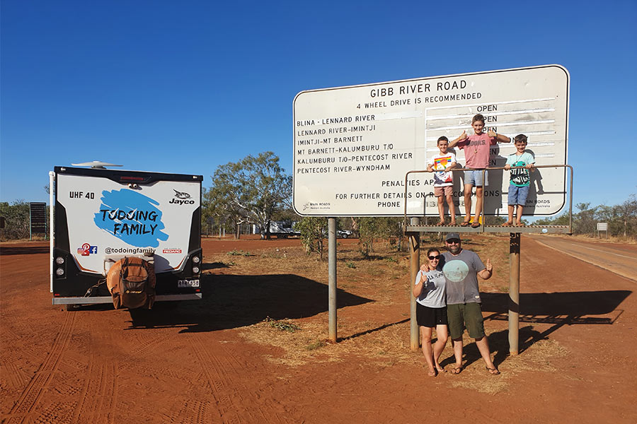 Family posing next to the Gibb River Road Sign along with their vehicle.