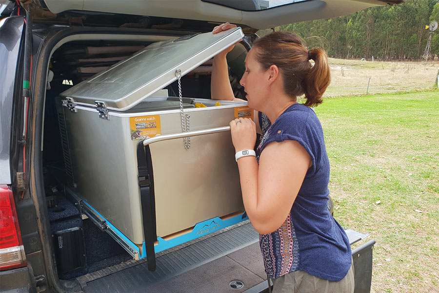Woman looking in fridge for food, located in back of vehicle