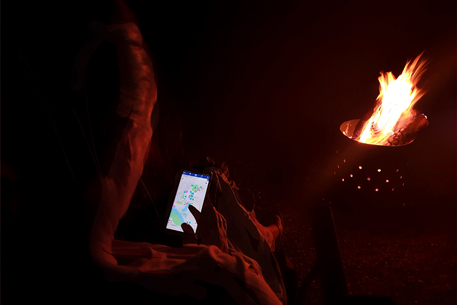 Woman looking at the Wikicamps app on her smartphone by the fire at night