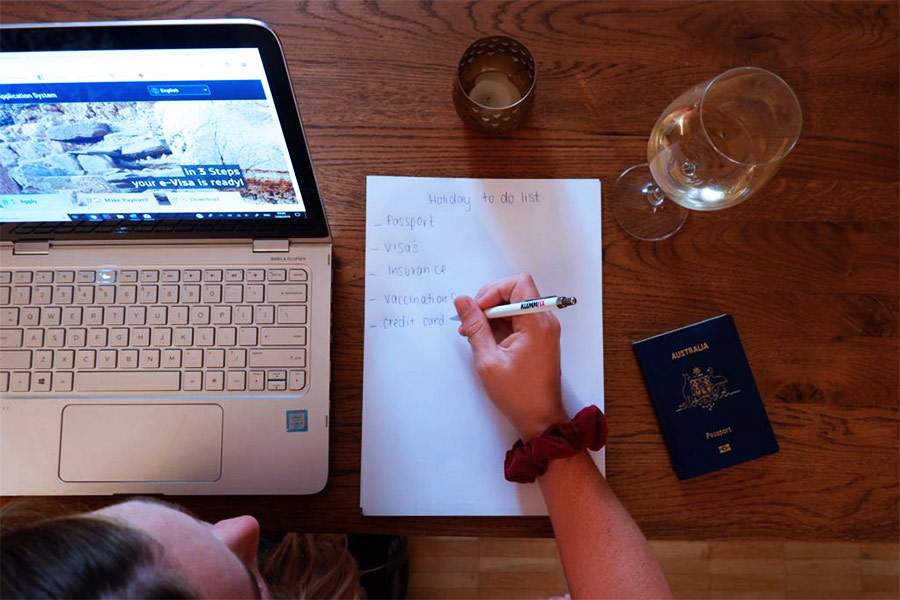 Woman writing travel prep checklist on a wooden table