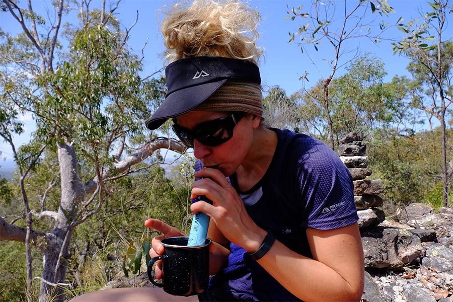 Woman drinking water out of a Lifestraw