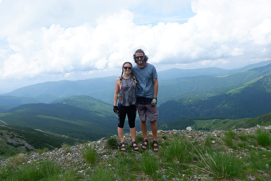 Couple posing for a photo on top of a mountain