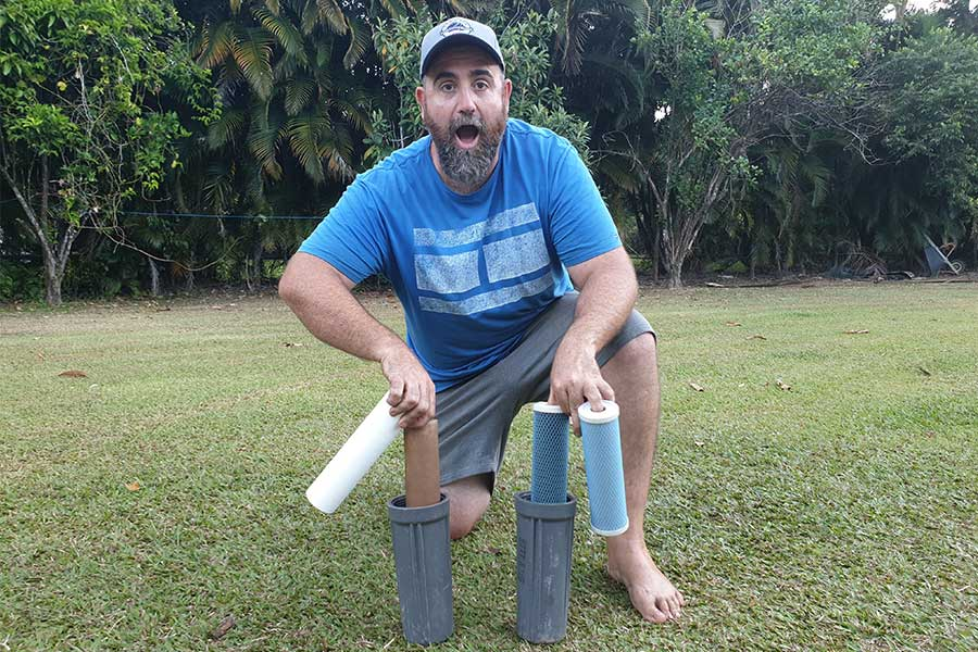 Man showing the difference between a used water filter and a new one