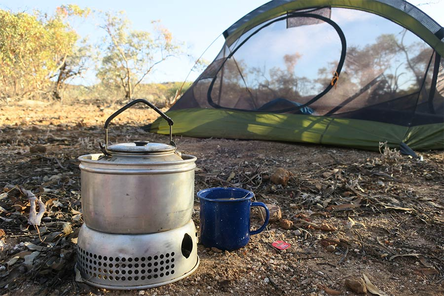 Boiling water next to a hiking tent setup