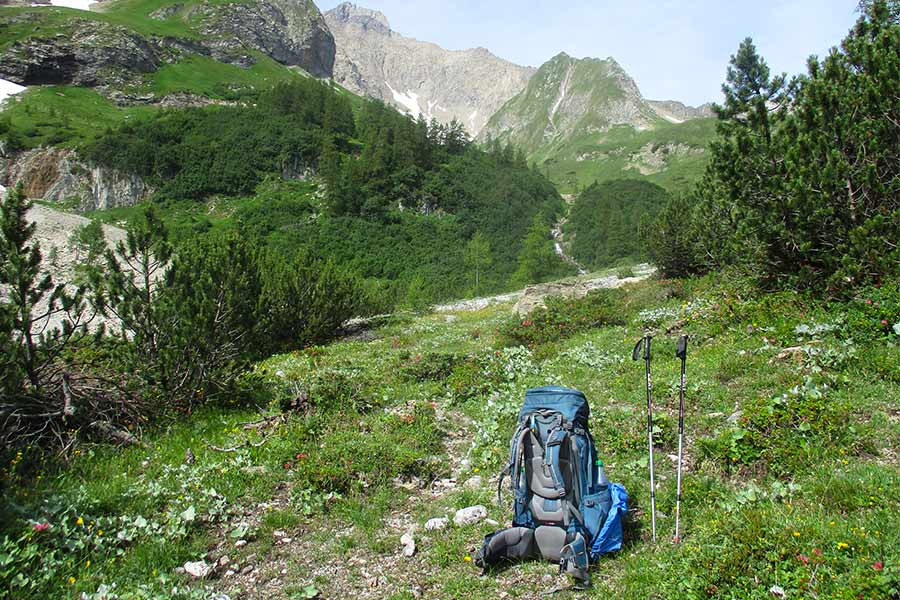 Deuter-Aircontact-75L and hiking poles on the ground next to a walking trail