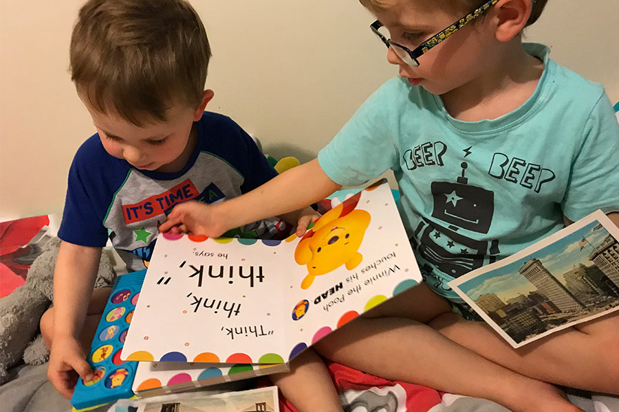 Two boys reading picture books on a bed