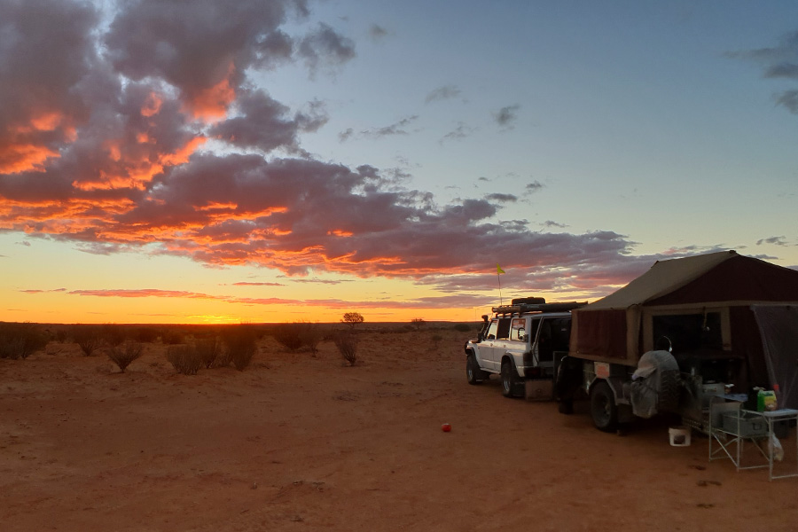 Vehicle next to camper trailer in the Simpson Desert at sunset