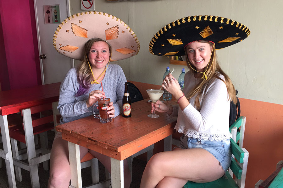 Two women sitting at a restaurant table drinking cocktails and wearing sombreros