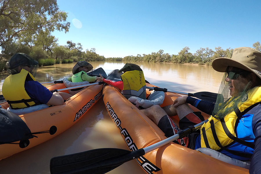 Two people kayaking down a river