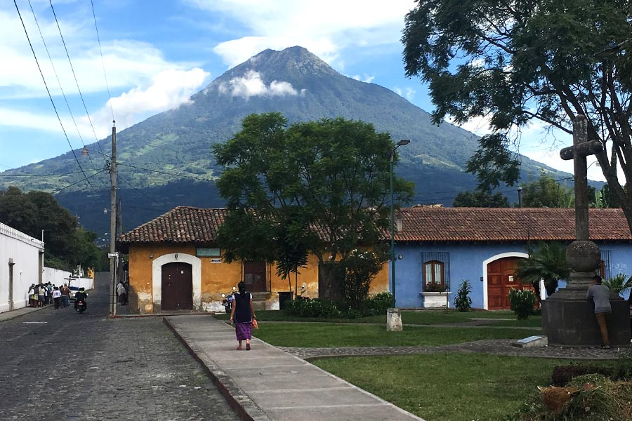 Woman walking towards house with volcano in the background