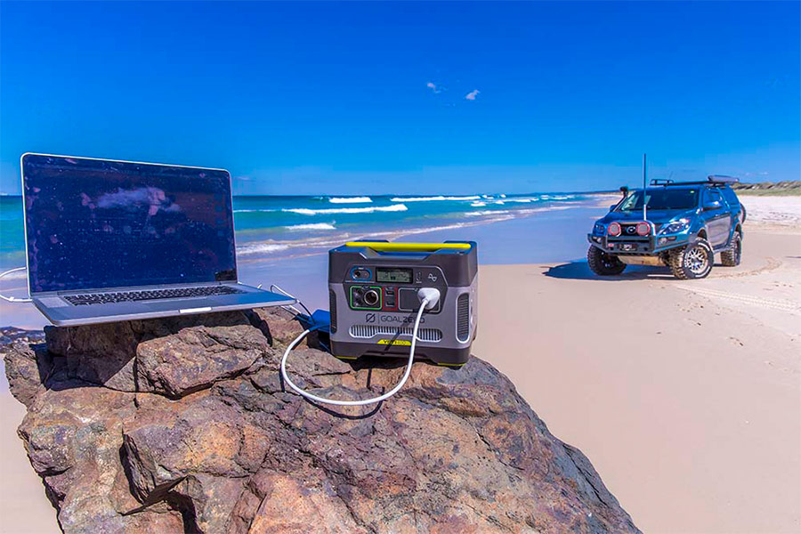 Laptop and power pack resting on a rock on the beach