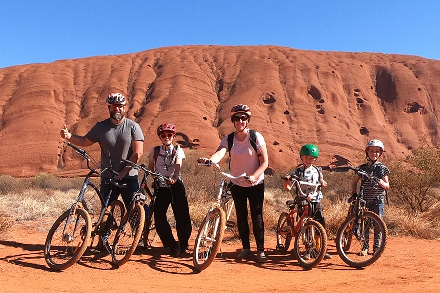 Family of 5 posing next to their bicycles with a giant red rock behind them