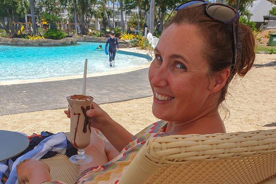 Woman drinking a chocolate milkshake by the pool