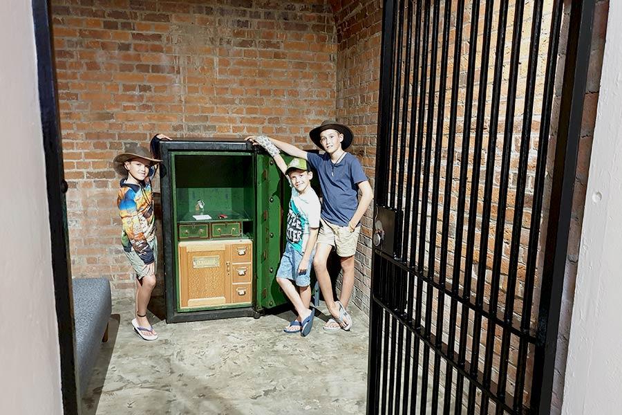 Three boys posing by a piece of furniture inside a jail cell