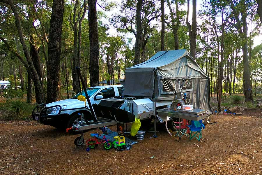 Hard floor camper trailer setup next to vehicle in the outdoors