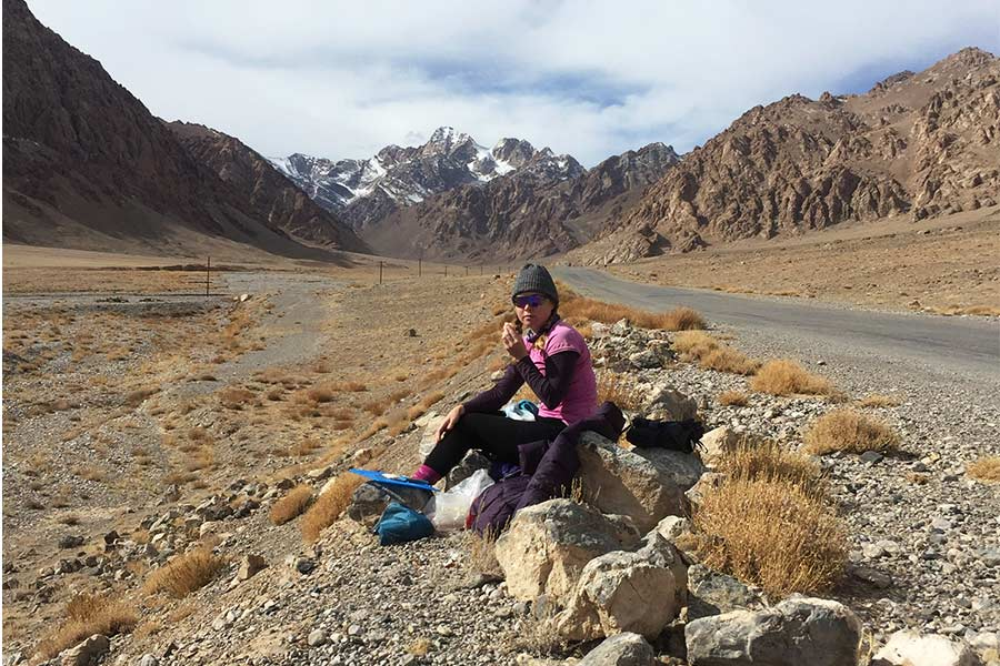 Woman sitting on a rock by the road having lunch in Tajikistan