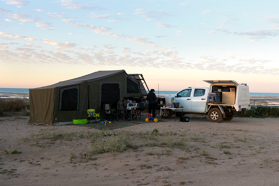 A soft-floor camper trailer setup next to 4wd at the beach