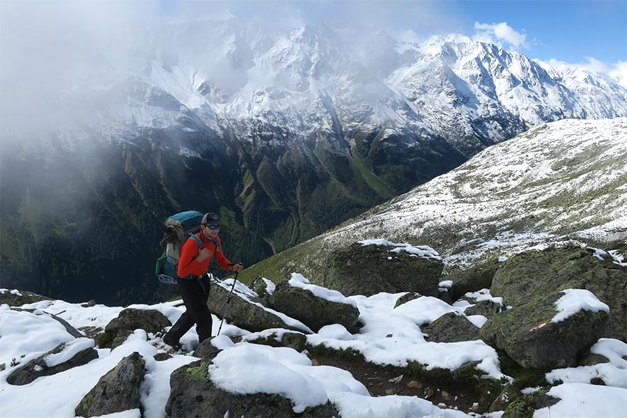 Man hiking up snowy mountain with hiking poles and a rucksack