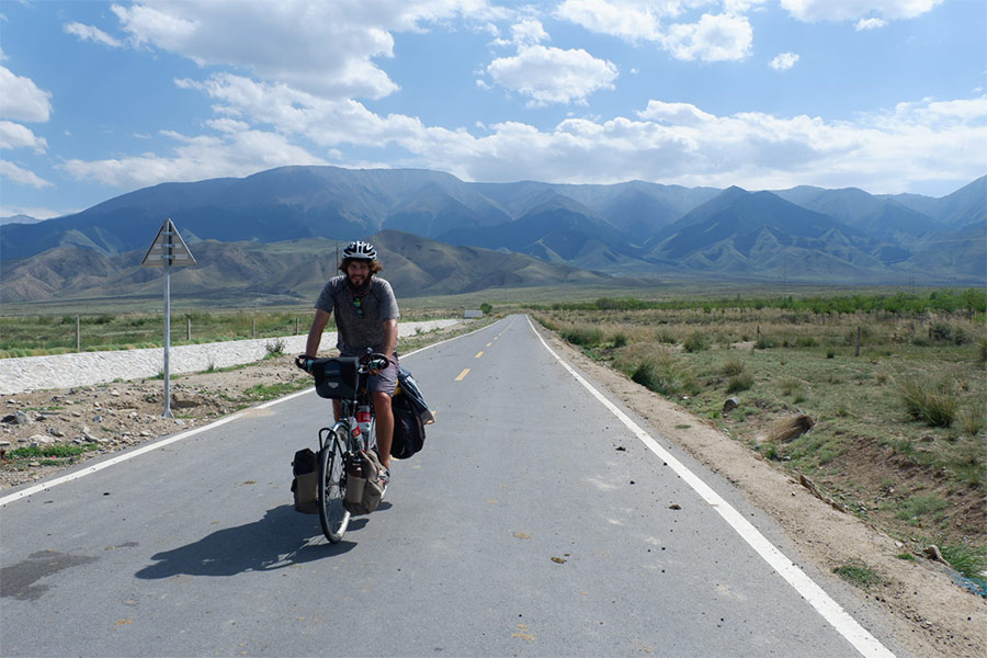 Man riding on bicycle on road in rural Western China