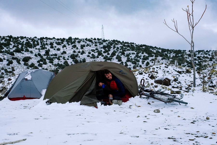 Man sitting in hiking tent in the snow along the Silk Road