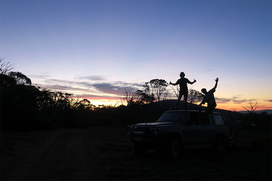 Two mates dancing on a 4wd in front of a sunset