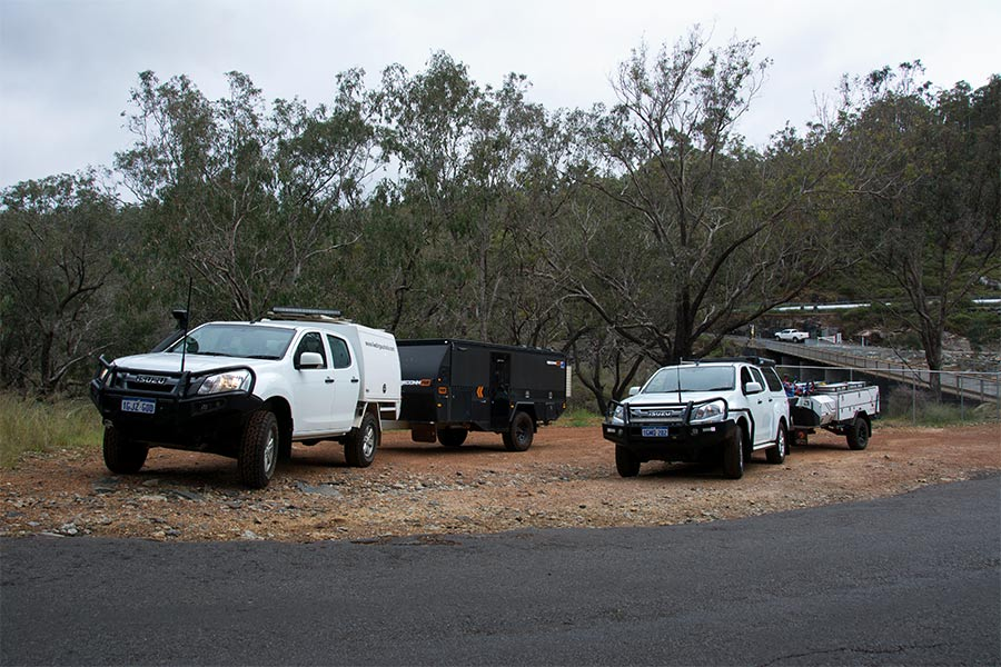 Two 4wds driving next to each other, each towing campers trailers at the rear