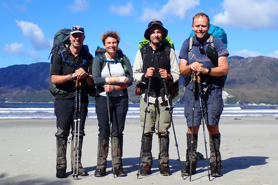 Four hikers standing together on a beach with their packs on