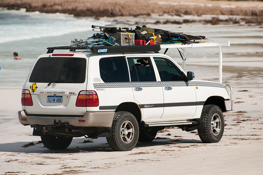 A giant roof rack attached to a 4wd driving down the beach